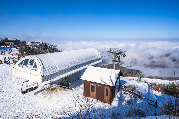Winter of Deogyusan mountain at Muju Ski Resort in South Korea. Winter Snow Cold Temperature Nature Sky Architecture Plant Day Environment Building Exterior Built Structure Tree Outdoors Fuel And Power Generation White Color Blue Transportation Industry Land Snowcapped Mountain