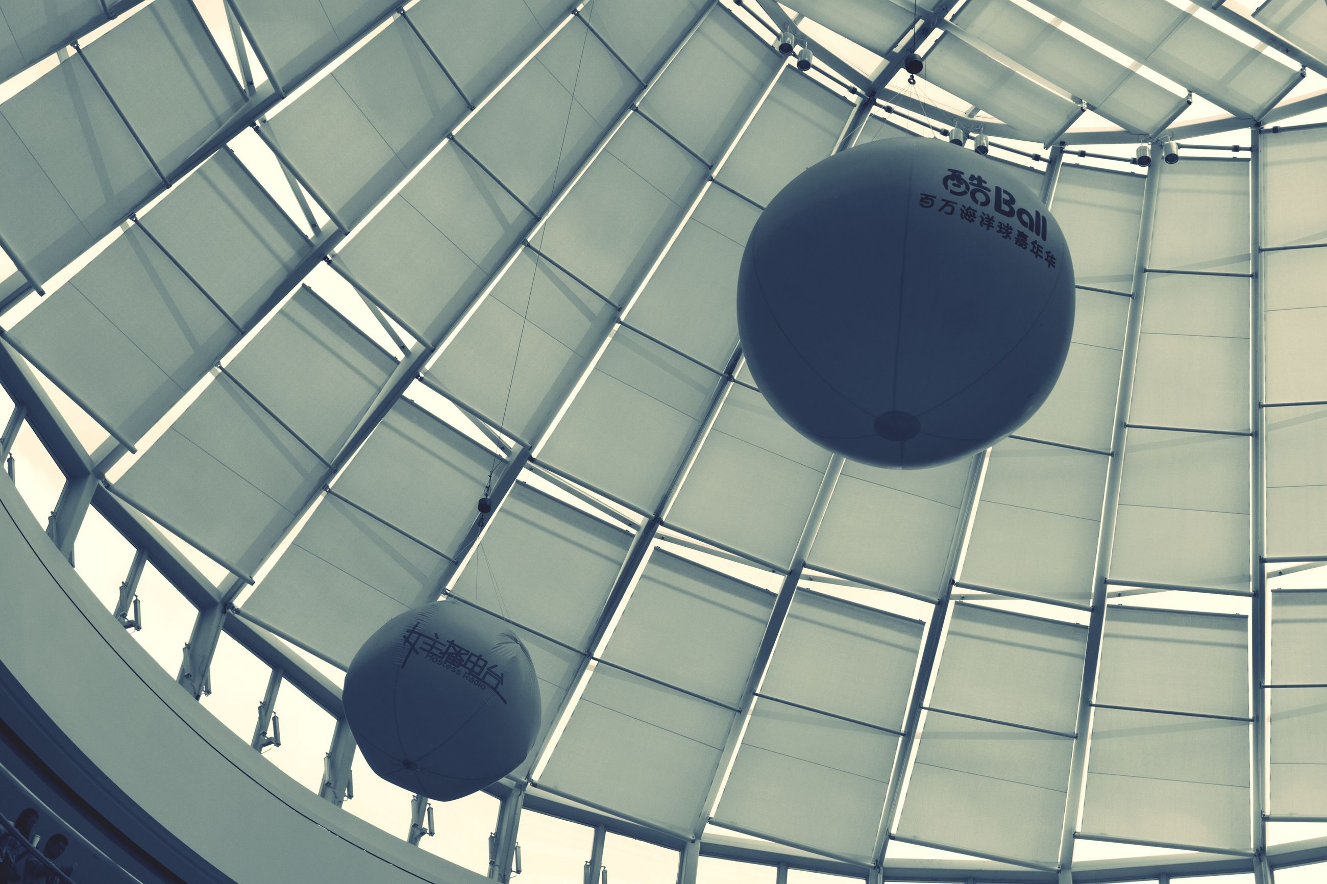 indoors, built structure, architecture, low angle view, communication, text, ceiling, pattern, geometric shape, metal, no people, wall - building feature, hanging, circle, western script, modern, day, building exterior, building, shape