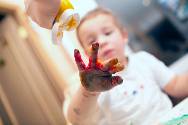 Close-up of messy child playing with paints