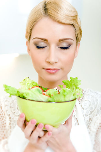 Beautiful young woman with vegetable salad. Dieting Concept. Vegetarian food Apron Attractive Woman Beautiful Woman Blond Hair Bowl Caucasian Diet Dieting Dinner Eating Female Healthy Eating Healthy Lifestyle Holding Indoors  Kitchen Lifestyles Meal Time One Person One Young Woman Only Salad Vegetables Vegetarian Food Young Adult Young Women