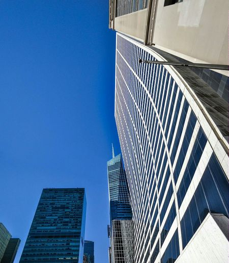 Low Angle View Of Bank Of America Tower And Skyscrapers Against Clear Blue Sky