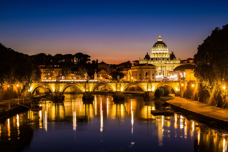 Illuminated bridge over river against st peter basilica at night
