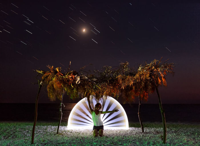 Woman kneeling with light painting at beach against sky