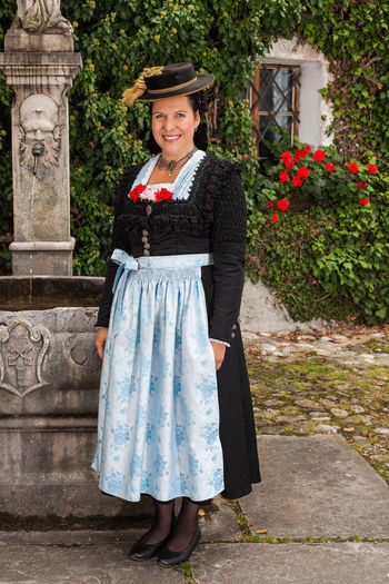 Smiling German woman in traditional costume wearing a dirndl and hat standing outside the entrance, to a creeper clad house Berchtesgadener Land  Traditional Culture Adult Adults Only Bavarian Charming Cheerful Costumes Day Dirndl Front View Full Length Happiness Looking At Camera Mature Adult One Person One Woman Only Only Women Outdoors Portrait Schalk Smiling Standing Tourism Traditional Costume