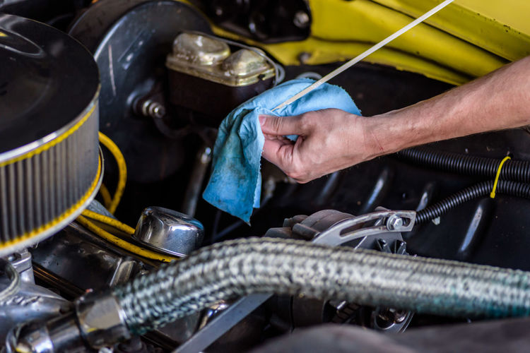 Cropped hand of man repairing car engine