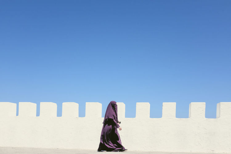 Woman with a burka walking beside a white wall