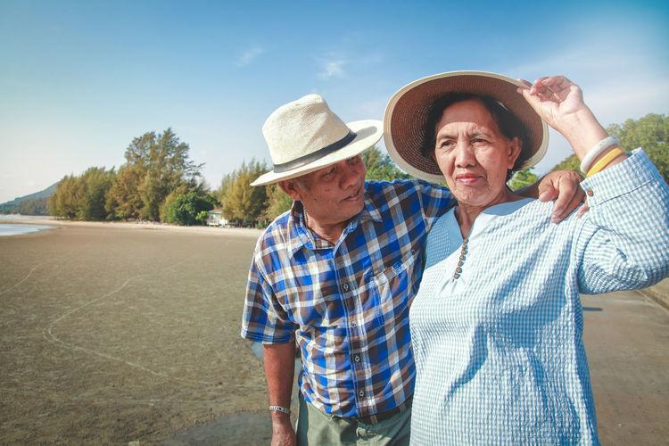 Senior couple standing at beach against sky