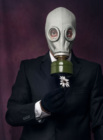 Portrait of man wearing gas mask while holding flower against black background