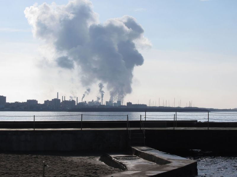 Industrial landscape along the coast. Air polluting factory chimneys Atmosphere Beach Cancer Chemical Chimney Coast Critical Danger Dangerous Dirty Emission Energy Environment Factory Industrial Pipe Pollution Sea Smog Smoke Steam Terrible Toxic Unhealthy Warming