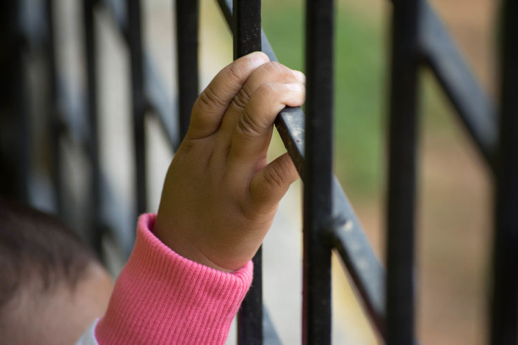 Cropped image of child hand holding metal grate