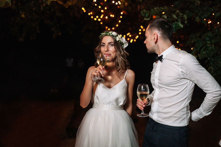 Portrait of couple holding wineglasses while standing outdoors at night