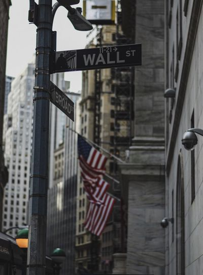Wall Street Wall Street  Wall Street In New York City New York Building Exterior Architecture Built Structure Communication Sign City No People Text Flag Building Road Sign Road Outdoors Street Guidance Low Angle View Street Name Sign