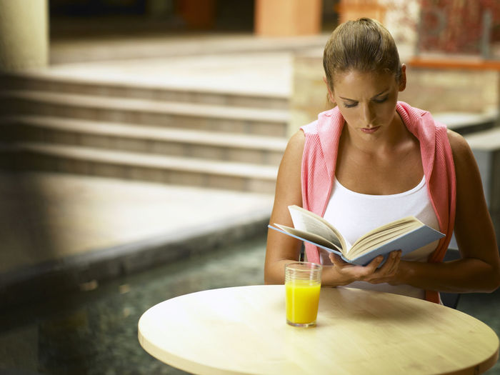 Young Woman Reading Book At Outdoor Restaurant