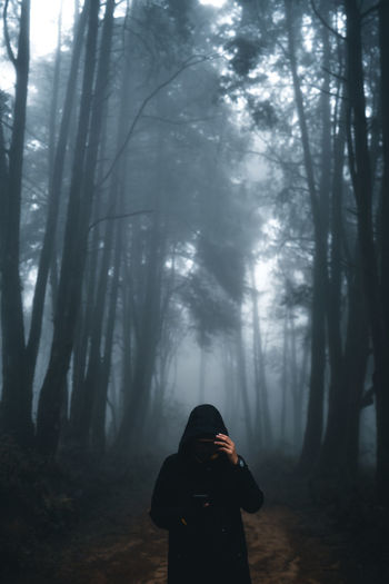 Man standing in forest against trees