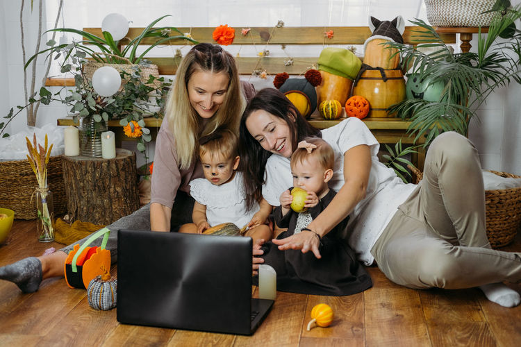 Cheerful mothers with daughters doing video call on laptop at home
