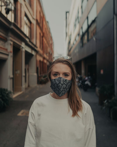 Portrait of young woman wearing mask standing outdoors