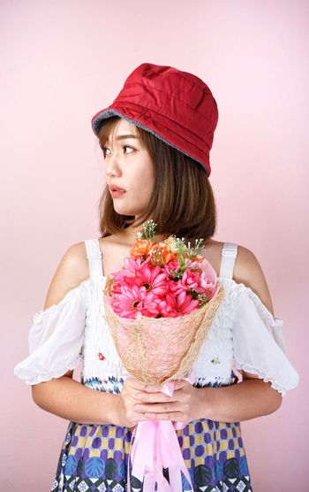 Woman holding bouquet against pink background
