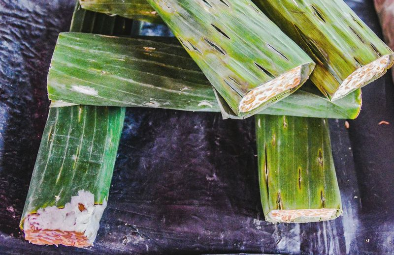 tempe on the local market Tempe Soy Product Banana Leaf Indonesian Food Indonesian Market Food Organic Vegetarian Food No People High Angle View Wood - Material Green Color Day Outdoors Close-up