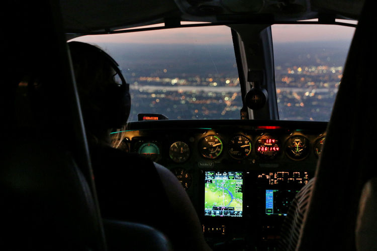 Rear view of pilot in airplane during sunset