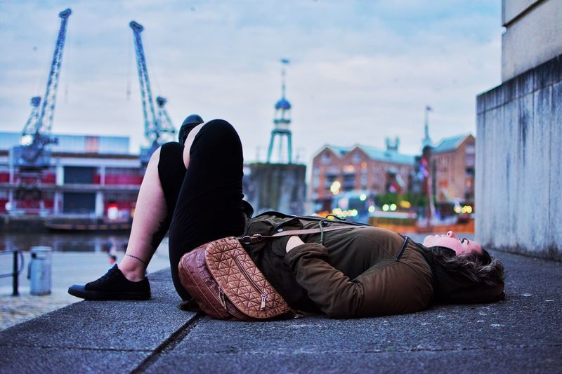 Young woman lying on footpath by river