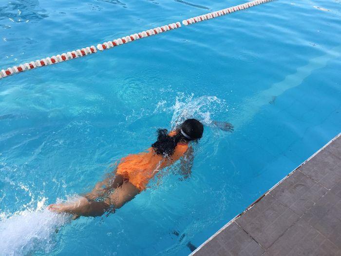 Rear view full length of girl swimming in pool