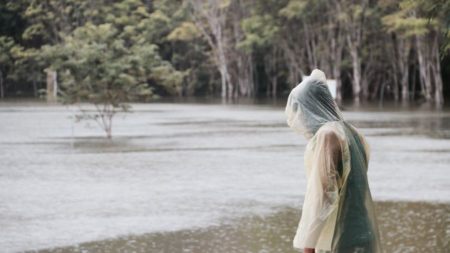 Side View Of Woman Wearing Raincoat While Standing By Lake During Rainy Season