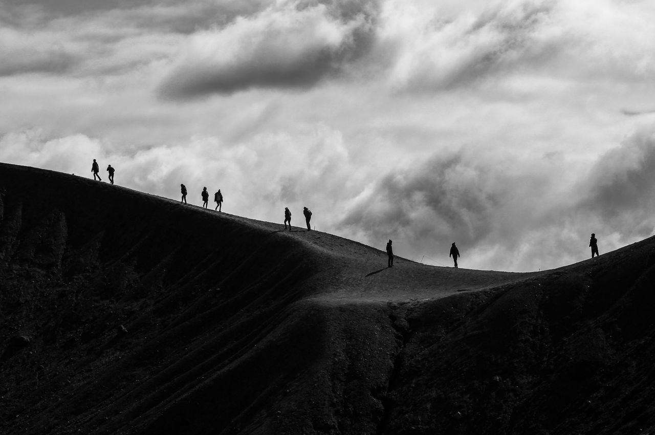 Low angle view of silhouette people standing on mountain against cloudy sky