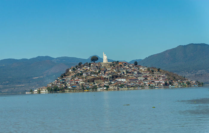 The island of Janitzio in Lake Patzcuaro, Michoacan, Mexico Beauty In Nature Blue Clear Sky Coastline Day Idyllic Island Janitzio Jose Morelos Lake Mexico Mountain Nature No People Outdoors Patzcuaro Rippled Scenics Sky Statue Tourism Tranquility Travel Destinations Water Waterfront