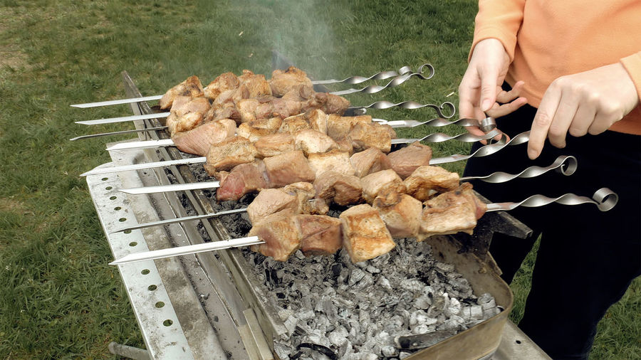 Woman Turning Skewers On A Grill