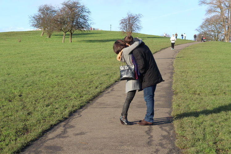 Full length of couple embracing on footpath in park