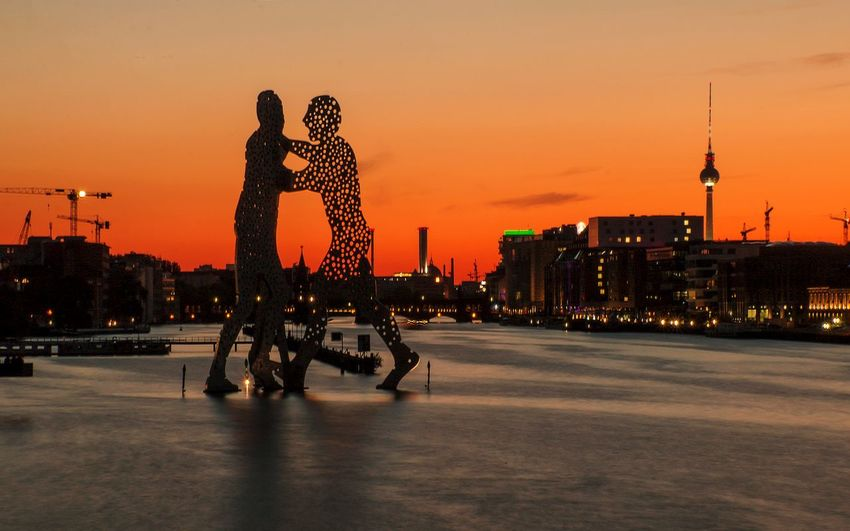 Silhouette people at illuminated city against sky during sunset