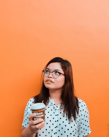 Woman looking away while holding drink against orange background