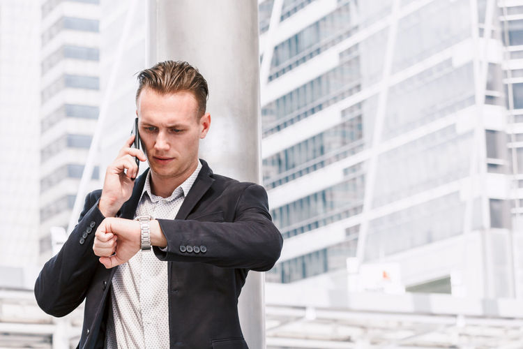 Young Businessman Talking On Mobile Phone While Checking Time Outdoors