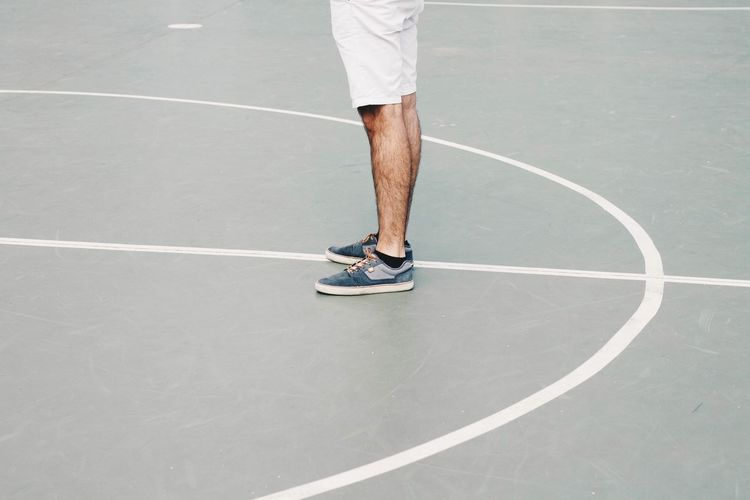 Low section of man standing on basketball court