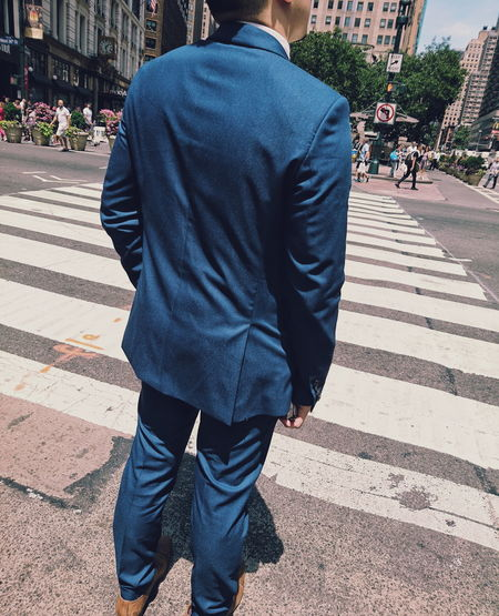 Rear view of businessman standing on zebra crossing in city during sunny day