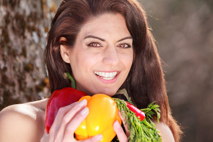Portrait of smiling young woman holding vegetables