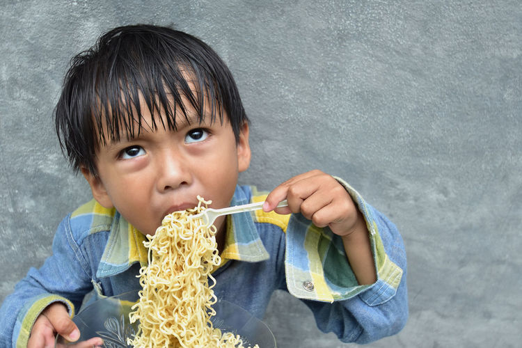 The picture of a boy eating a hungry noodle. The concept of eating children Boys Casual Clothing Child Childhood Food And Drink Front View Headshot Holding Indoors  Innocence Looking At Camera Males  Men Offspring One Person Portrait Wall - Building Feature