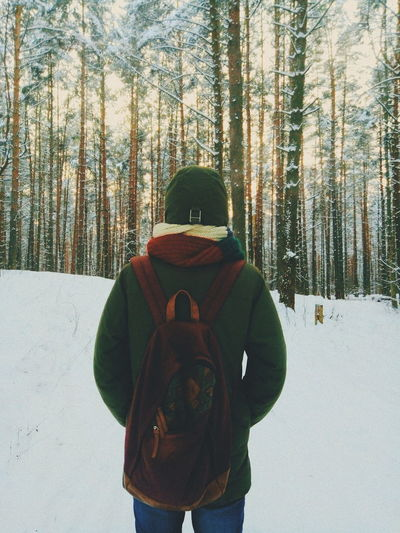Rear View Of Man With Backpack Standing In Snow Covered Forest During Winter