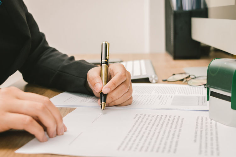 Midsection of businesswoman writing on document at office