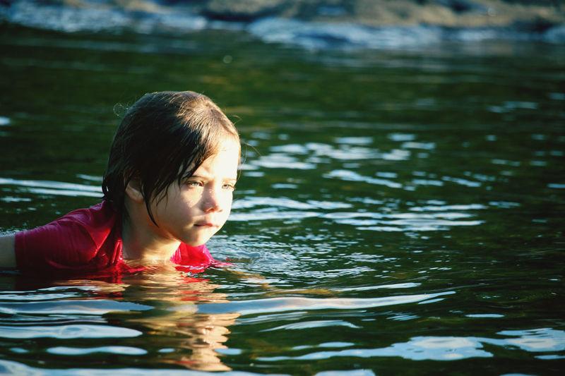 Portrait of boy swimming in lake