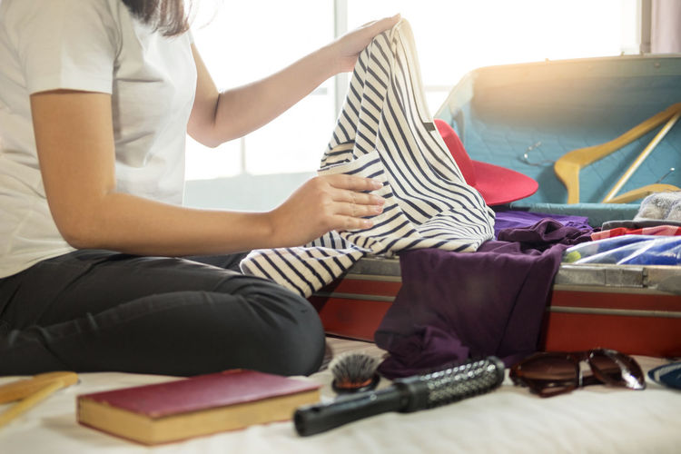 Midsection of woman packing suitcase