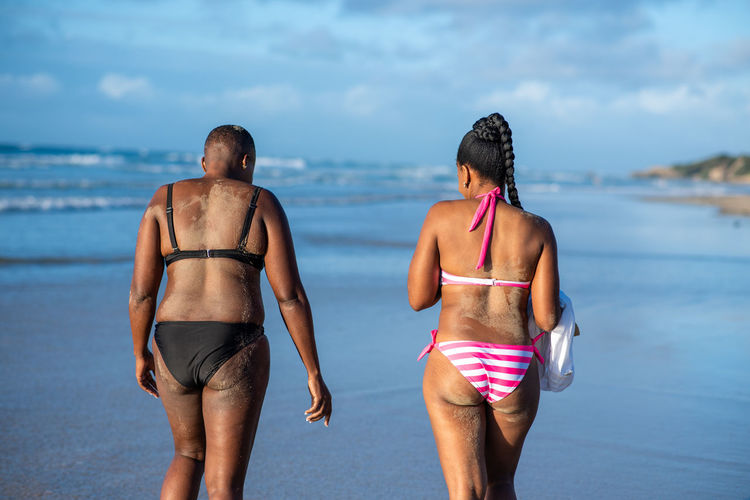 Rear view of friends enjoying at beach against sky