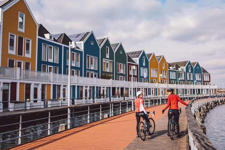 People riding bicycle by building against sky