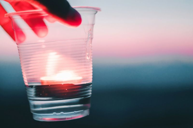 Cropped hand holding drink in disposable glass during sunset