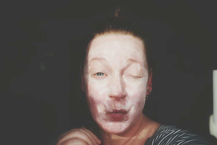 Close-Up Portrait Of Woman Wearing Face Mask While Making Face Against Black Background