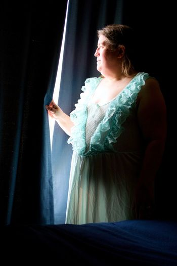 A beautiful middle-aged woman, in a lacy green nightgown, illuminated by window light.