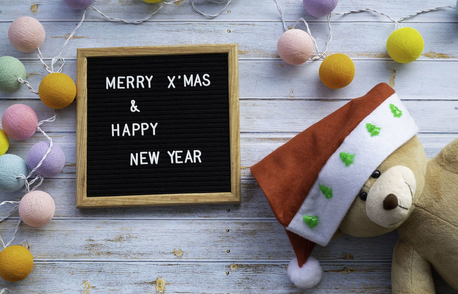 Teddy Bear Santa Hat Message Board Wooden Frame Greeting Words Christmas Decoration New Year Happy Merry Christmas! Text Alphabet Light Bulb Blue Wood Flooring Vintage Merry Theme Holiday POV Concept Still Life