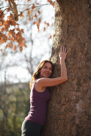 Portrait of woman with arms raised on tree trunk
