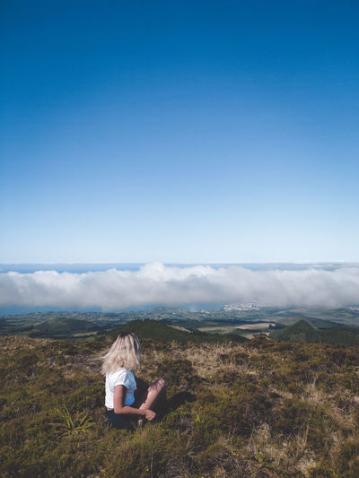 Woman sitting on landscape against sky