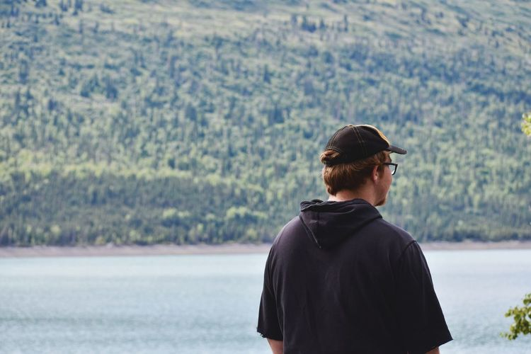 Rear view of man looking at lake by mountain